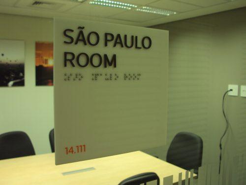 Placa em acrílico com vinil recortado, informações em alto relevo e braille